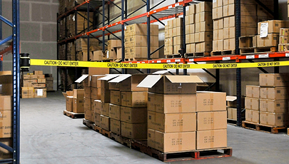 image of cardboard boxes in warehouse behind safety barrier