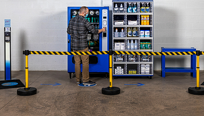 image of person using vending machine behind safety barrier
